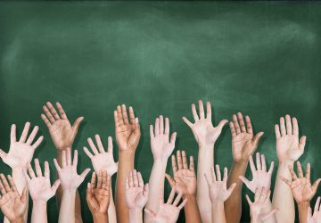 Diverse raised hands in front of blackboard